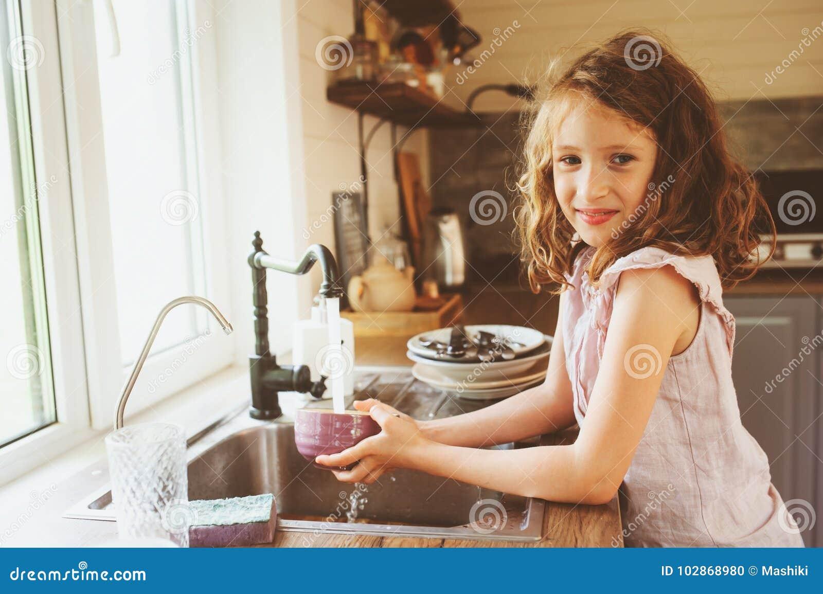儿童女孩在厨房里在家帮助母亲和洗涤盘 在真正的内部的偶然生活方式