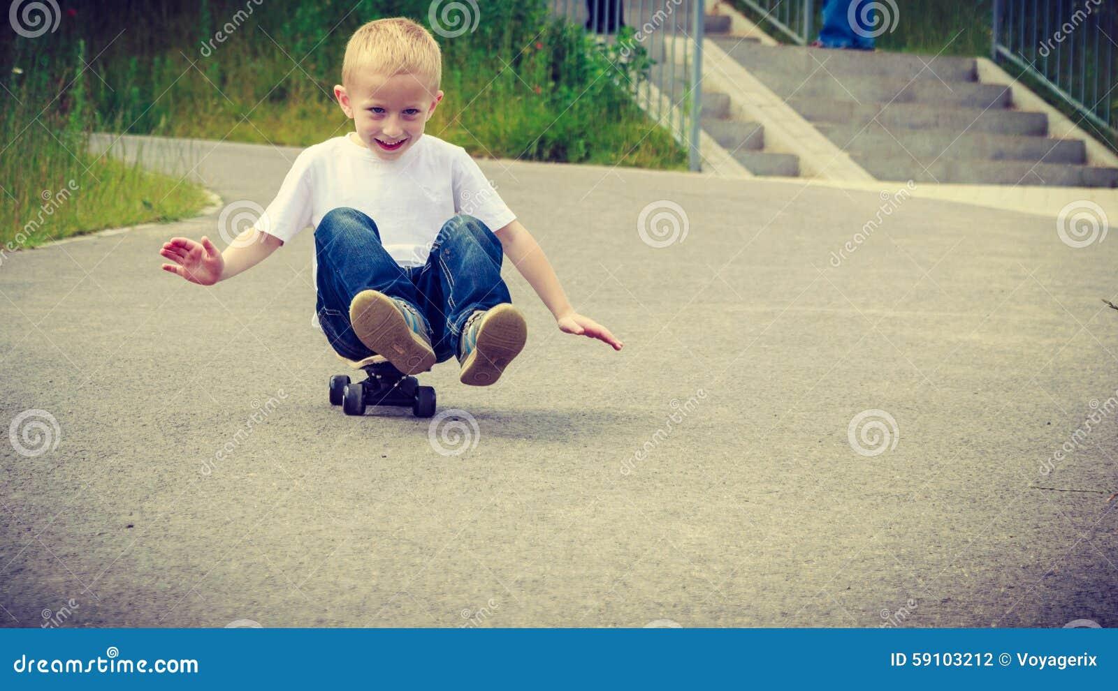 儿童孩子坐获得的滑板室外的乐趣