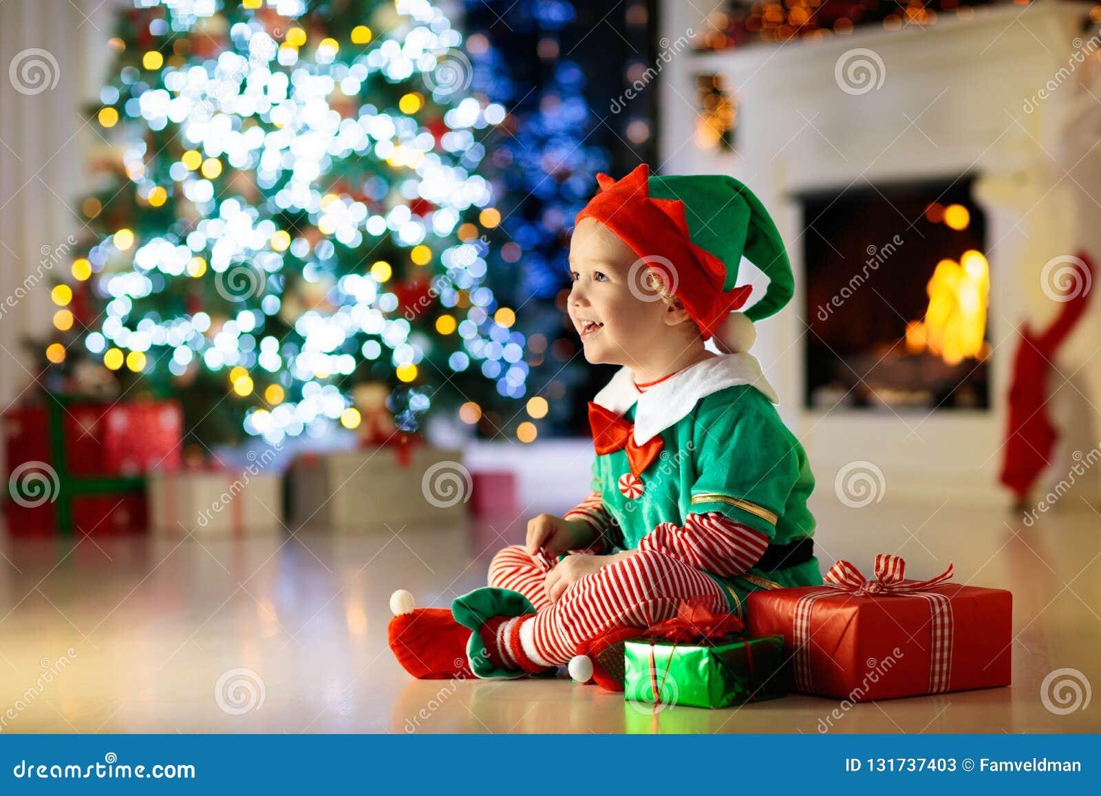 儿童打开当前在圣诞树在家 在矮子服装的孩子有Xmas礼物和玩具的 一点有礼物盒的男婴和