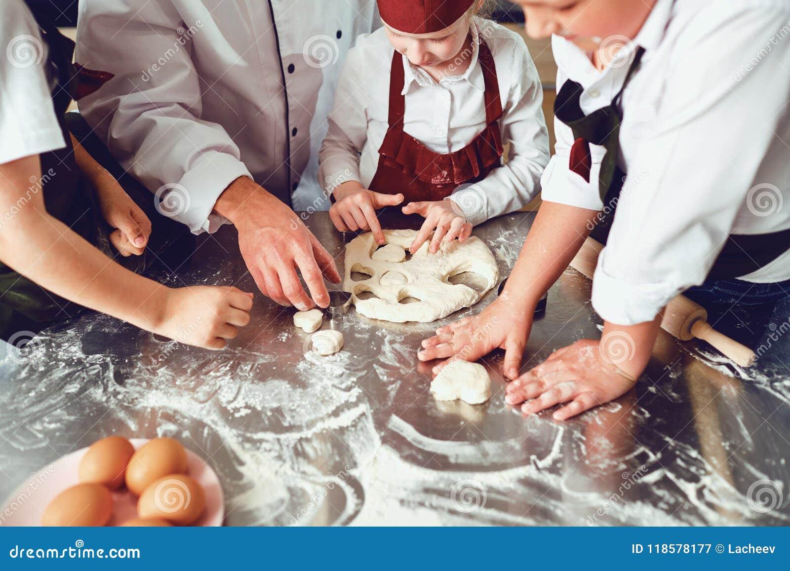 儿童特写镜头的手烹调在桌上的一个曲奇饼