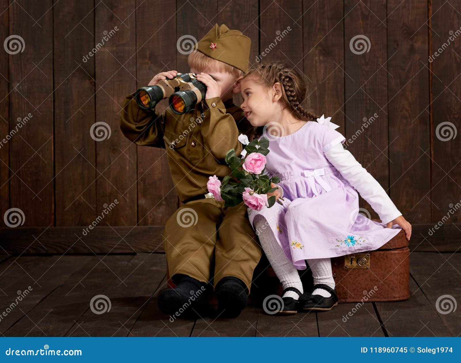 儿童男孩打扮作为减速火箭的军服和女孩的战士桃红色礼服的坐老手提箱,黑暗的木backgroun