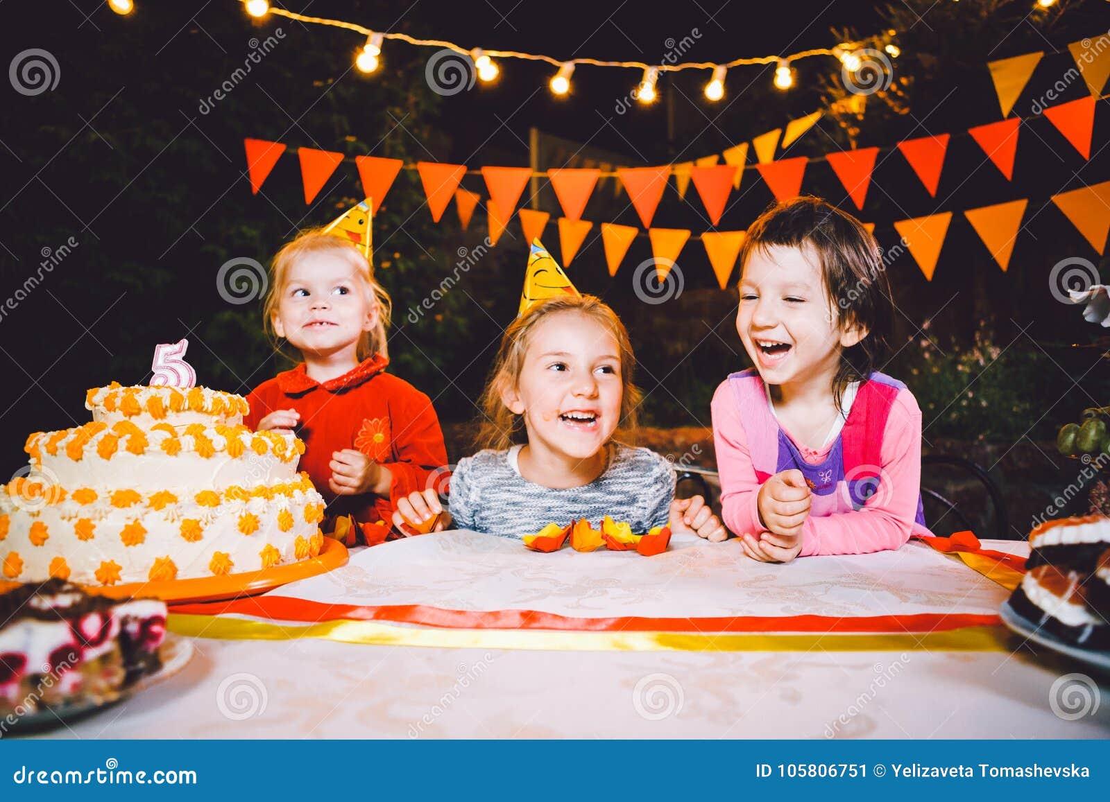 儿童` s生日聚会 在桌上吃蛋糕用他们的手和抹上他们的面孔的三个快乐的儿童女孩 乐趣a