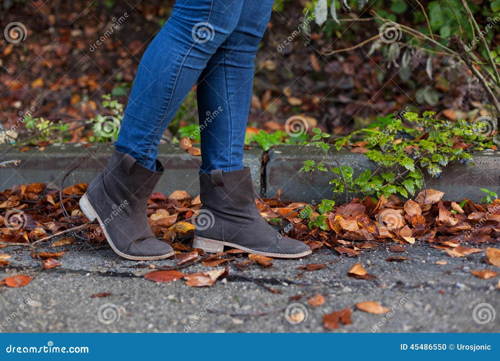充分走在街道上的妇女叶子在秋天期间