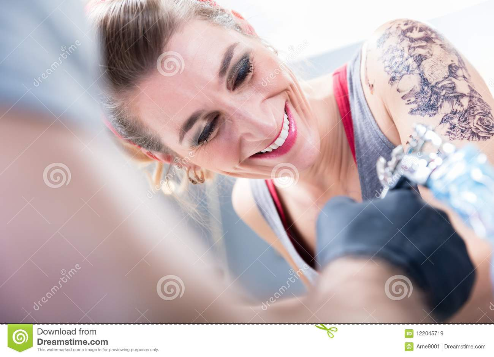 充满信心地微笑在一个现代纹身花刺演播室的快乐的妇女
