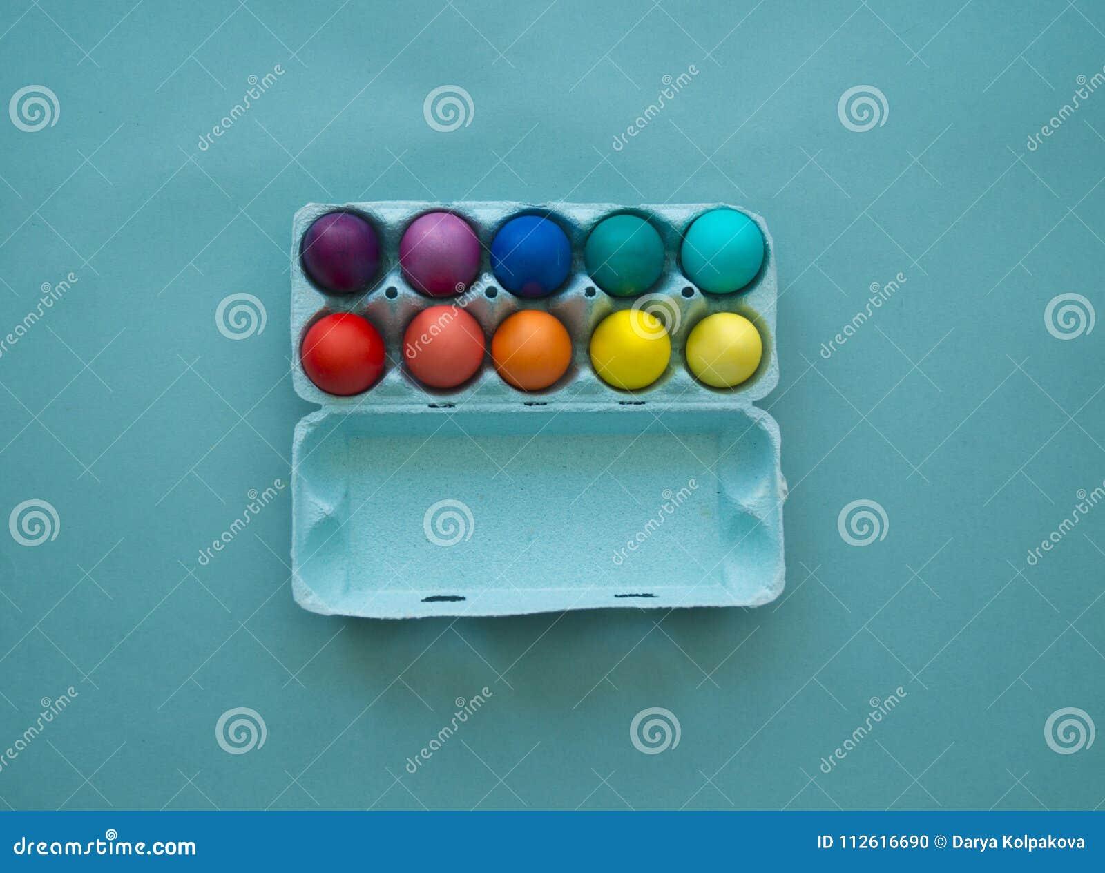 充满活力的手在被观看的纸板蛋盒的被洗染的五颜六色的复活节彩蛋