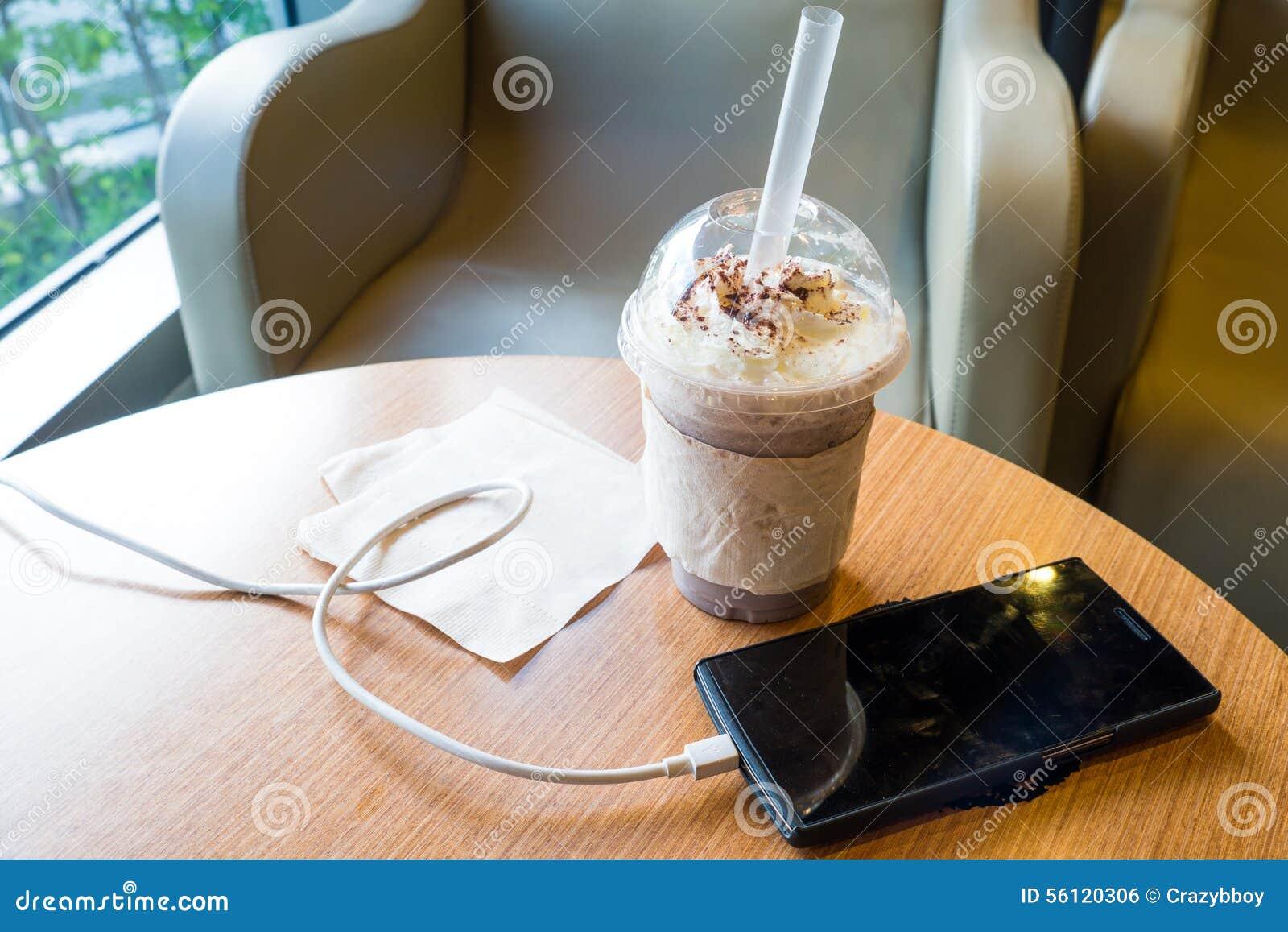 充电在咖啡馆的手机与塑料杯子被冰的巧克力frappe