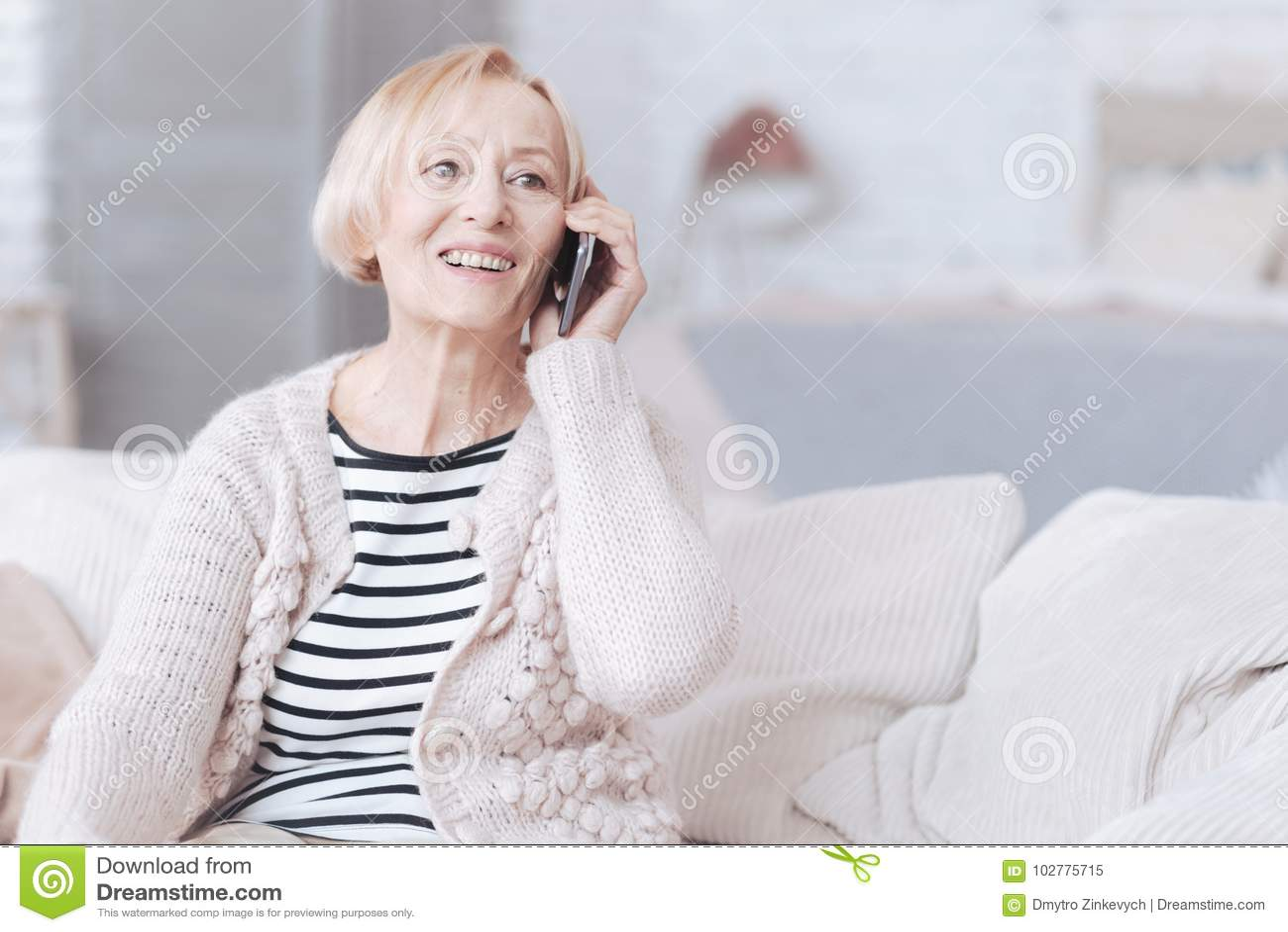 光芒四射的资深夫人在家谈话在电话