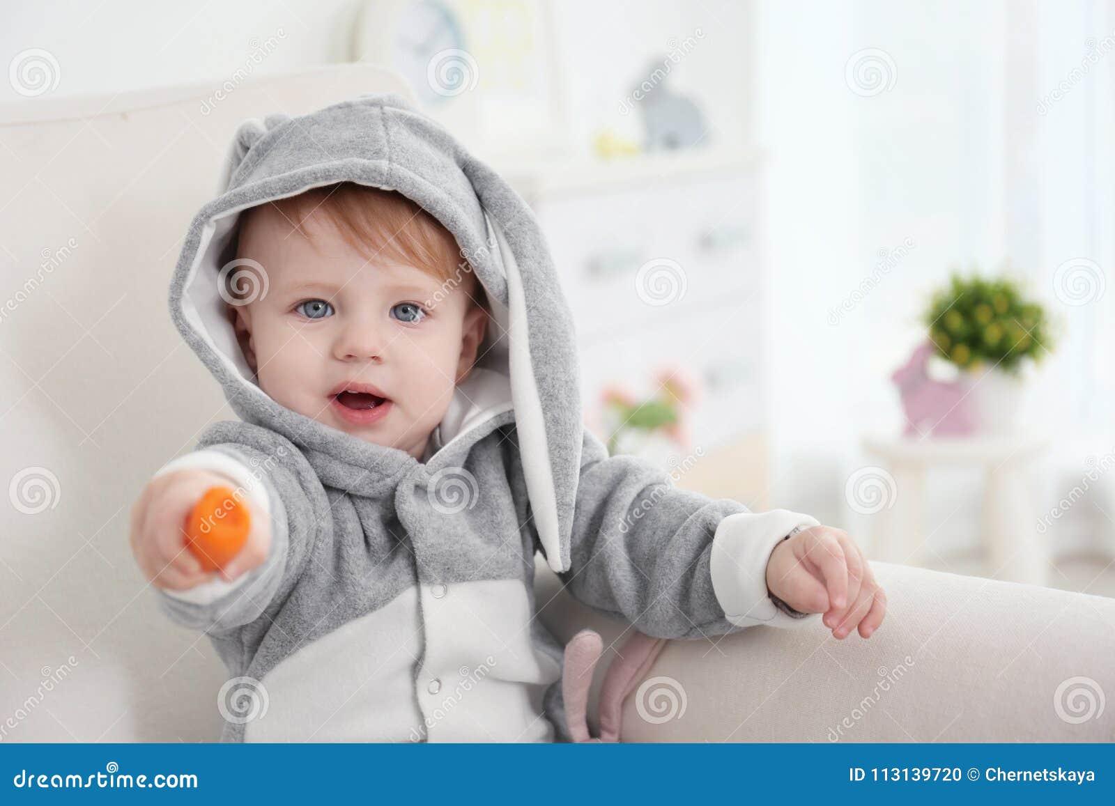 兔宝宝服装的逗人喜爱的矮小的婴孩用红萝卜