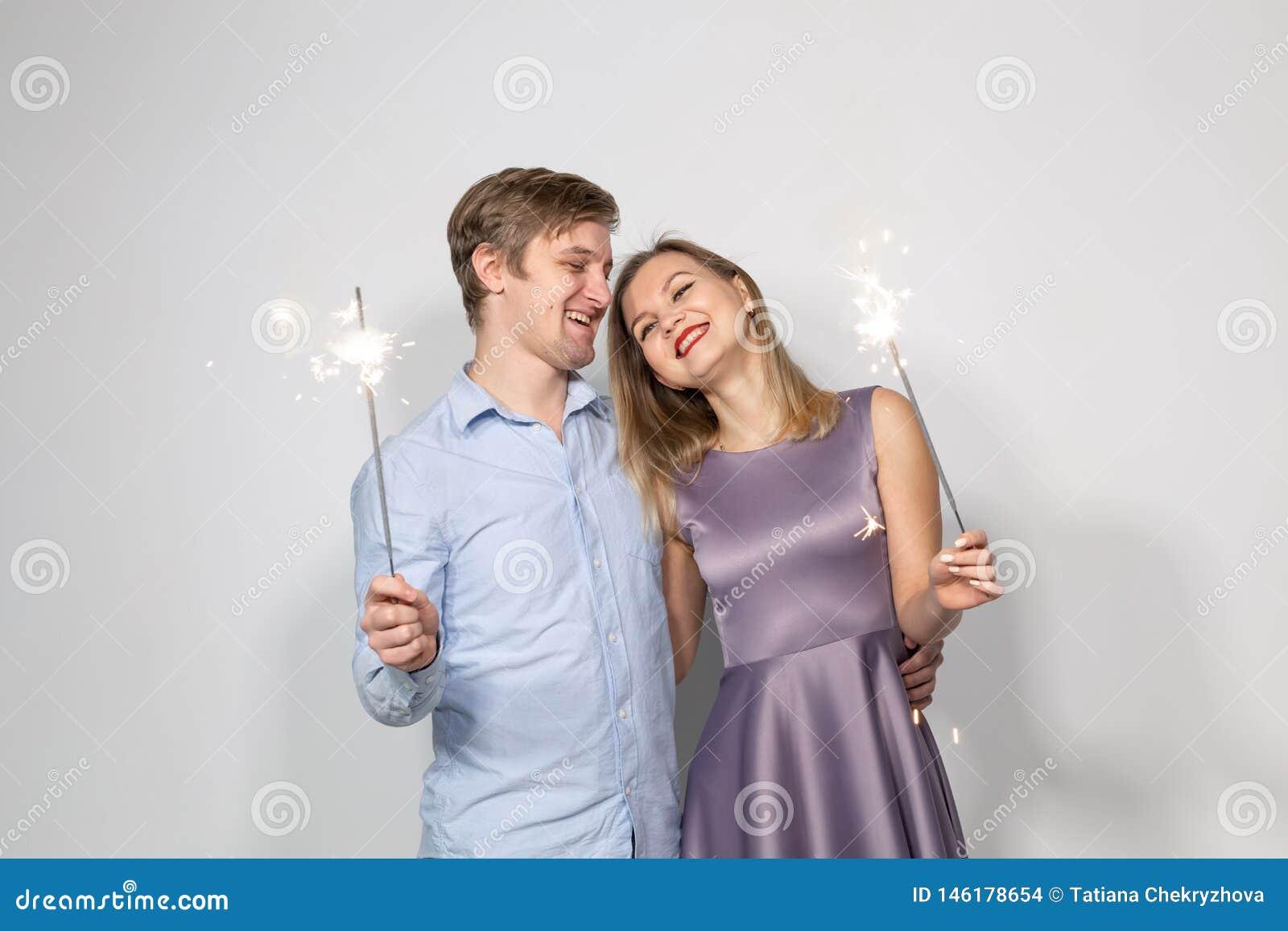 党、家庭和假日概念-拿着在白色背景的年轻夫妇闪烁发光物