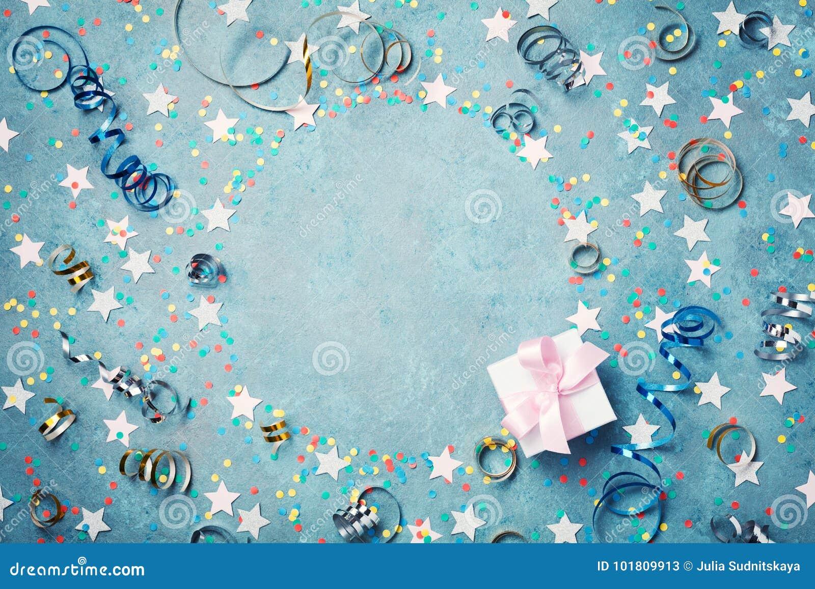 党、狂欢节或生日框架与五颜六色的五彩纸屑,礼物盒和飘带在葡萄酒蓝色桌上 圣诞节问候