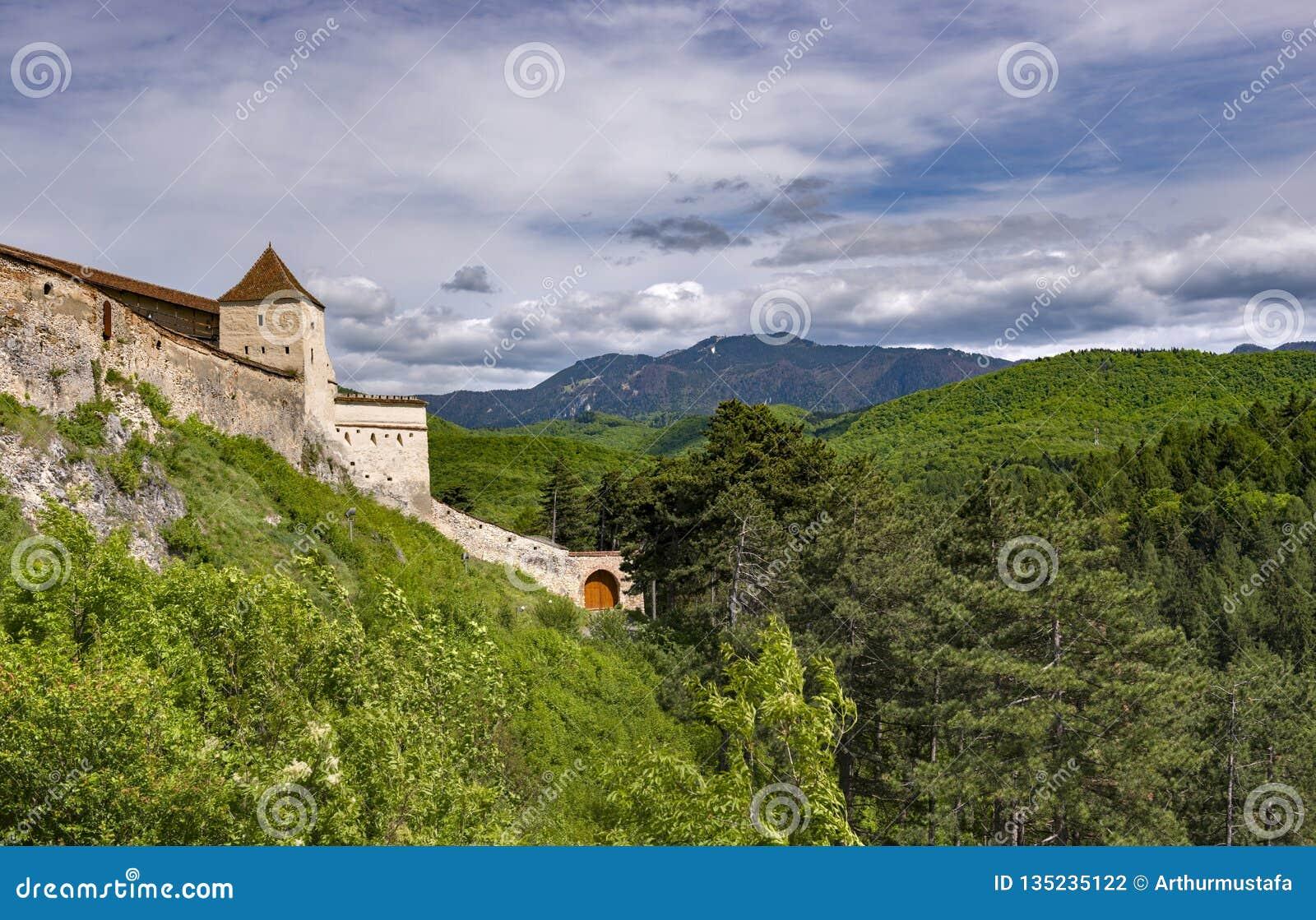 入口的美好的春天视图在Rasnov城堡在有波斯特瓦鲁山的布拉索夫县罗马尼亚,在背景中