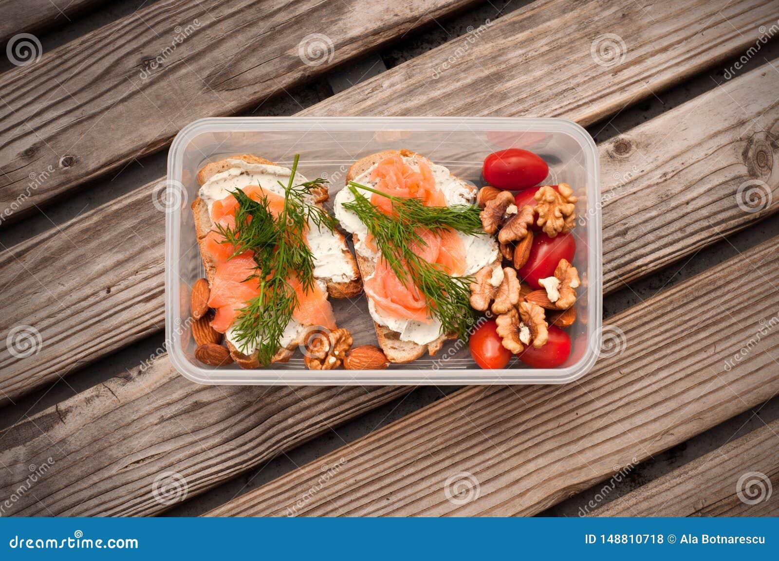 全麦面包用乳酪和三文鱼在塑胶容器 莳萝和杏仁用西红柿 健康三明治