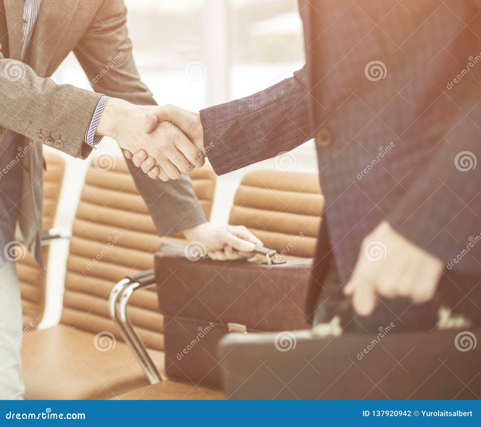 公司的雇员与握手在一个现代办公室的大厅的公文包的