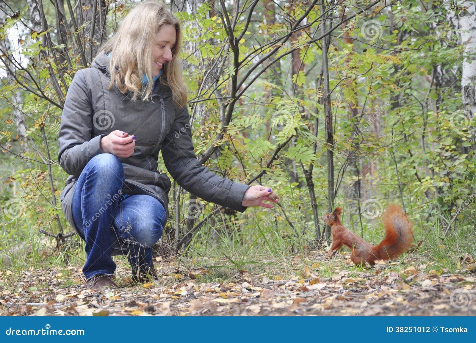 公园,喂养一只红松鼠的女孩。