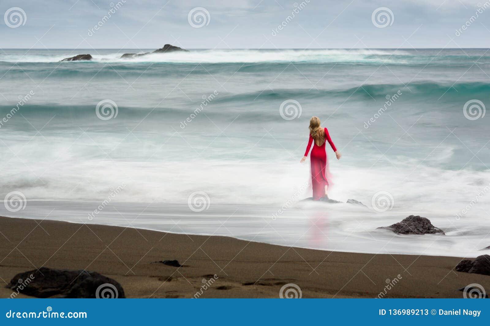 关于一名红色,长的加工好的美丽的白肤金发的妇女的艺术性的美术图片,在一个海滩岩石在水中站立