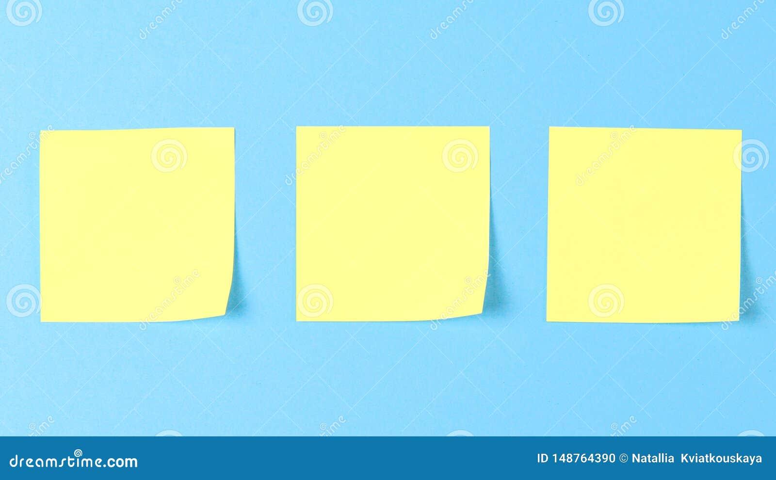 关于蓝色背景的空白黄色稠粘的笔记,企业工作的概念 在蓝色墙壁上的黄色备忘录贴纸 r