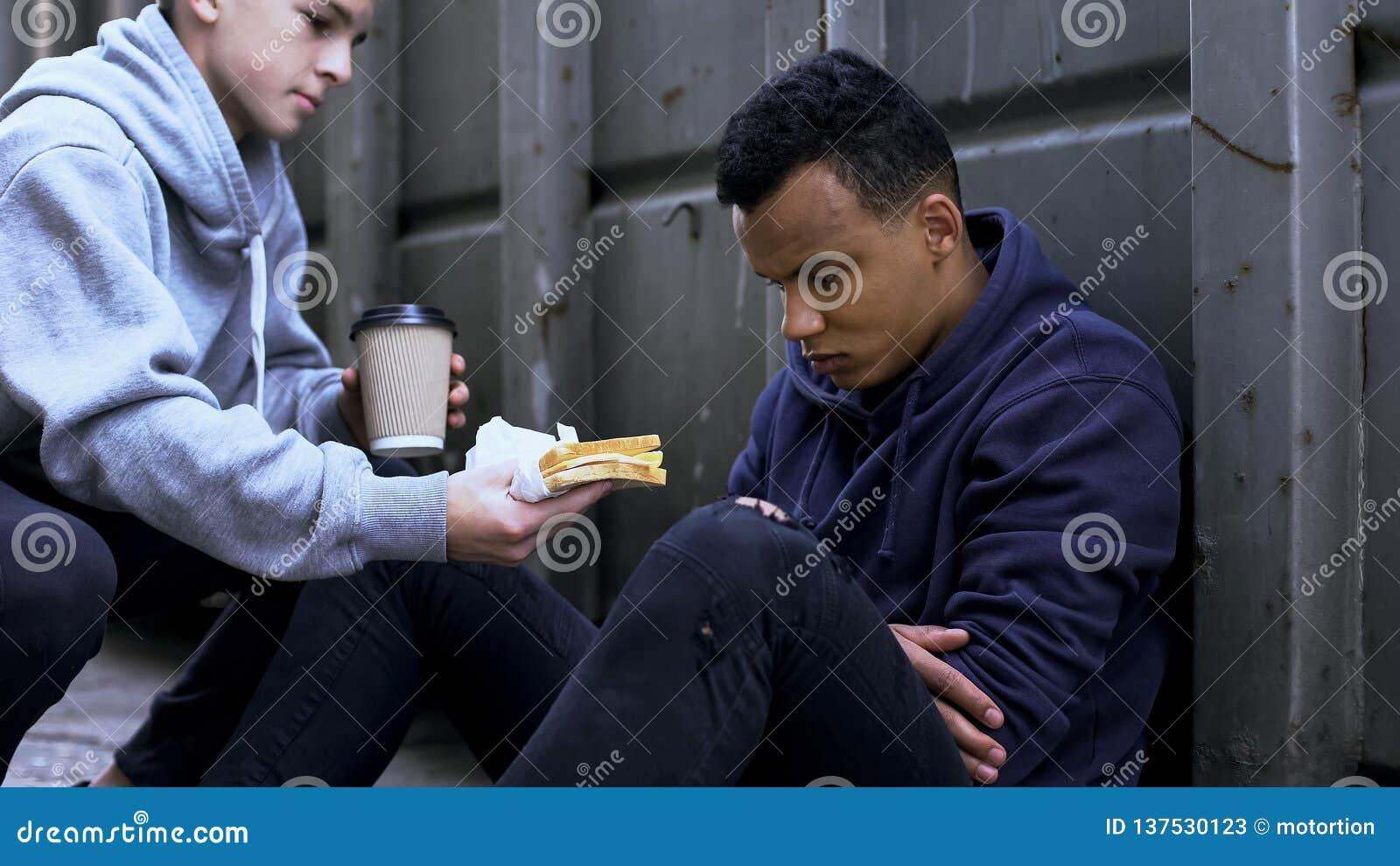 关心的志愿男孩给无家可归的少年,善良,慈善带来晚餐