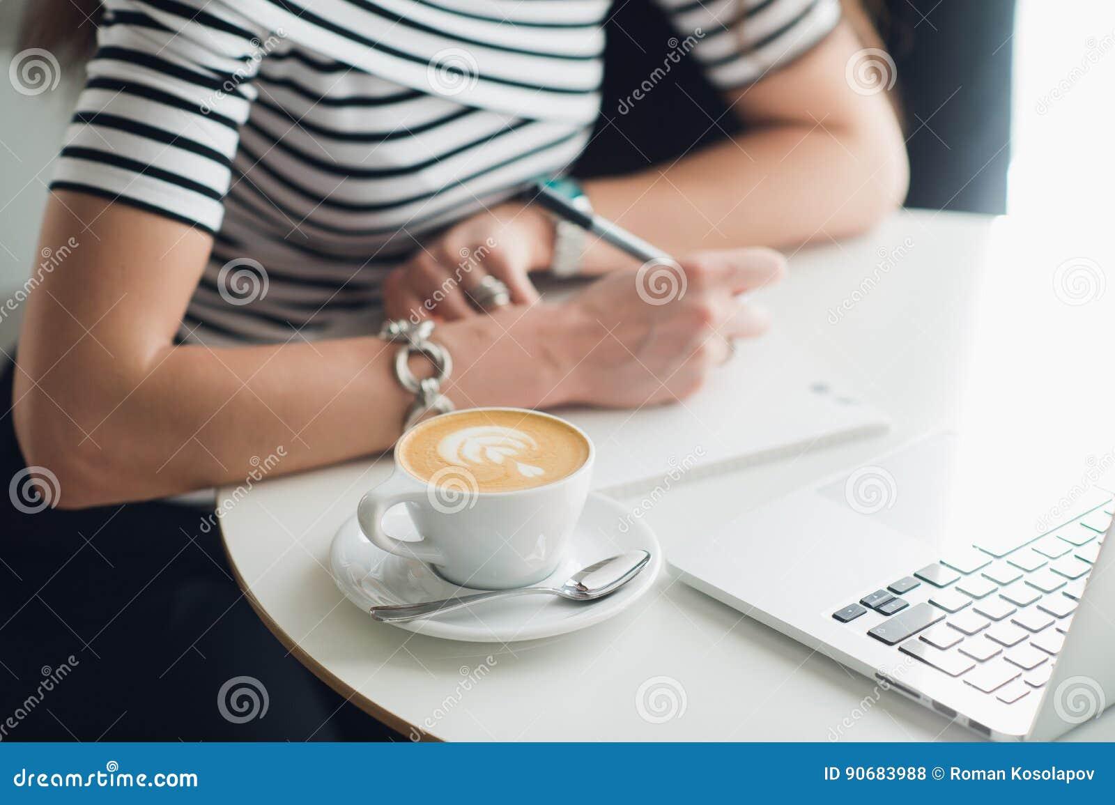 关闭一个杯子的图片与写在笔记本的样式和手的热奶咖啡 坐在咖啡馆woth a的妇女