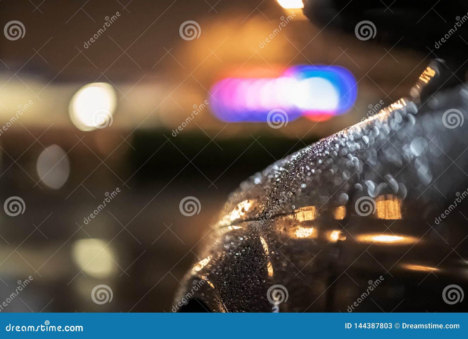 关闭一辆剧烈的黑汽车在晚上,等待在路灯到底在大雨中