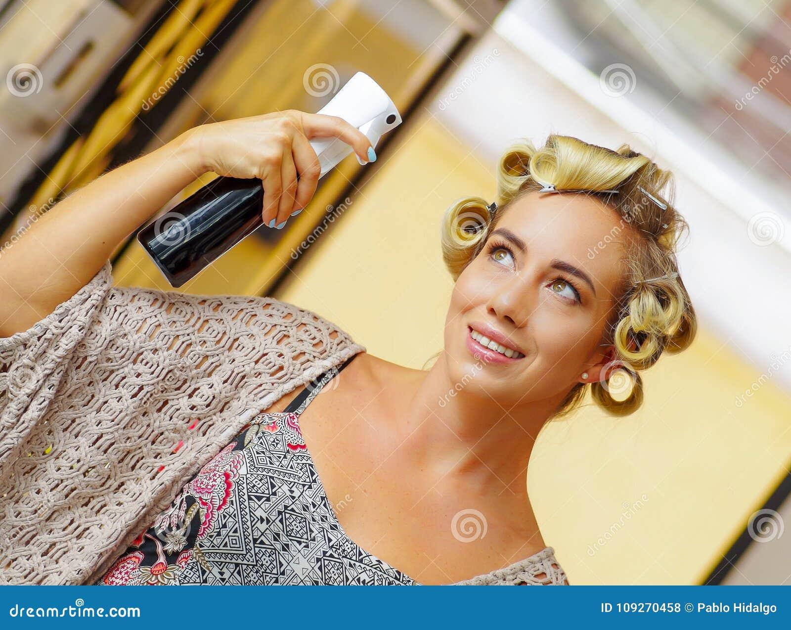 关闭与发胶的年轻白肤金发的妇女定象发型在理发美容院,在被弄脏的背景中