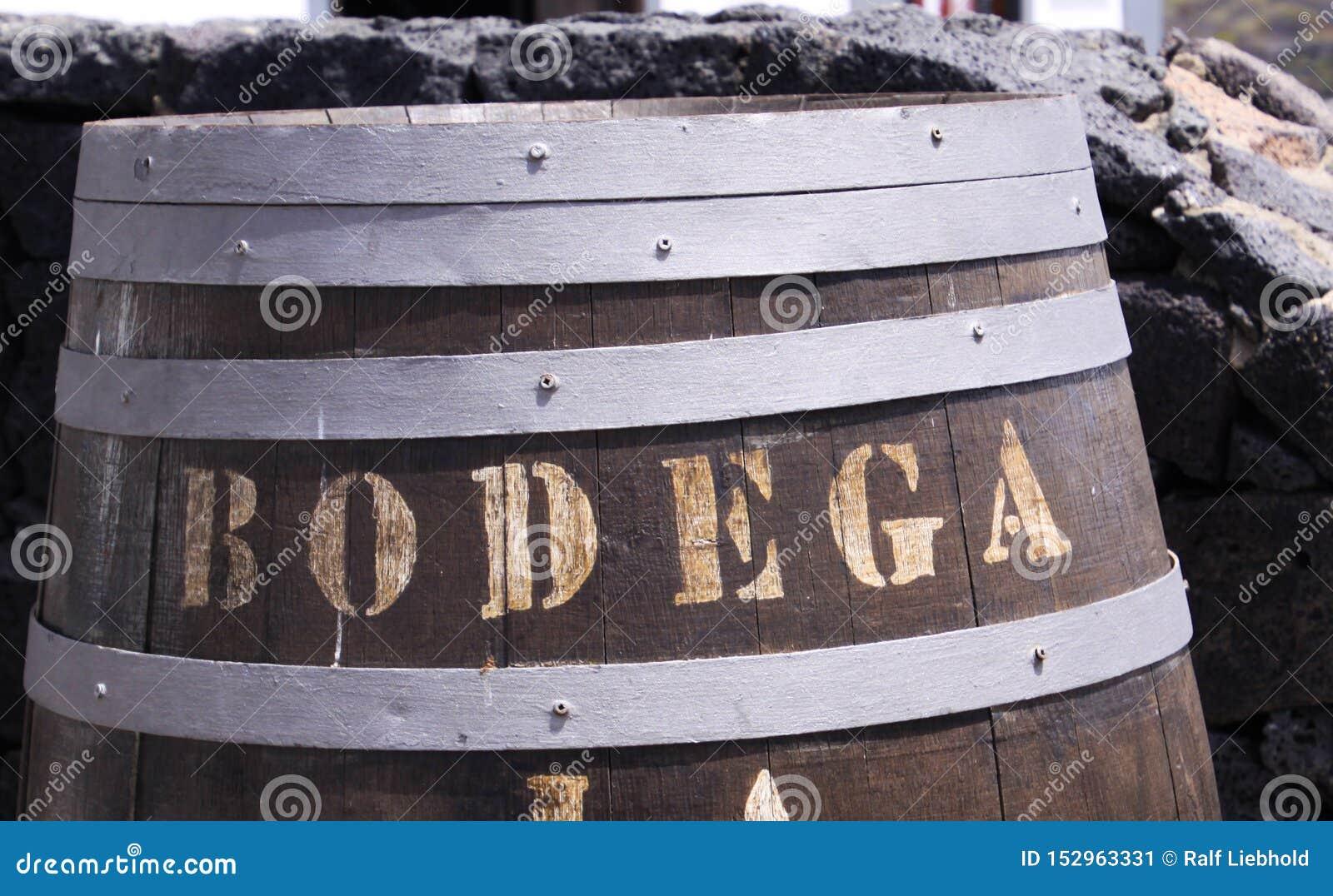关闭与文本杂货店的木葡萄酒桶在自然石墙-兰萨罗特岛前面
