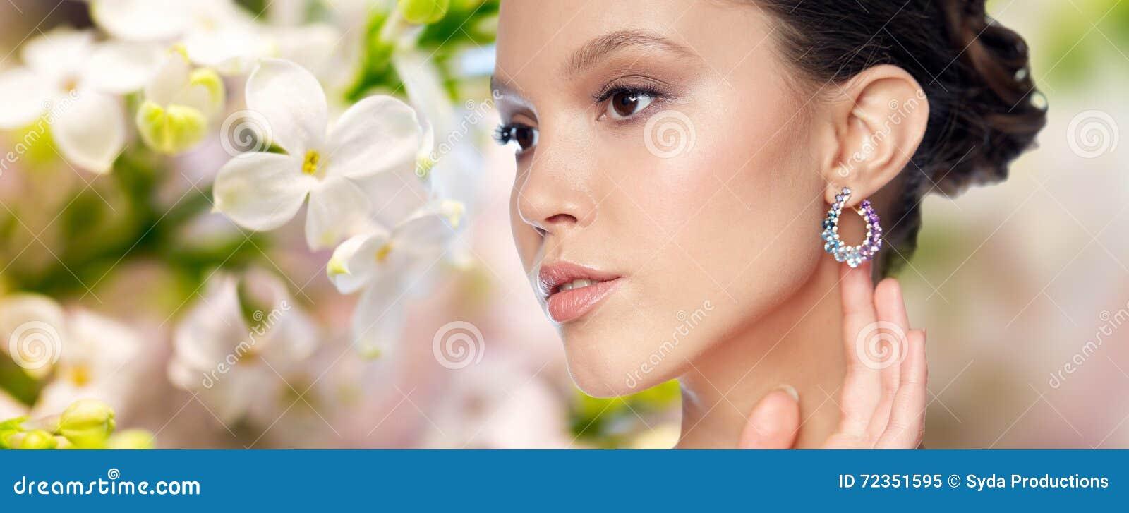 关闭与耳环的美丽的妇女面孔