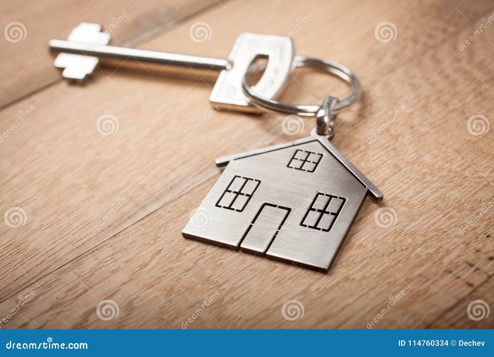 关闭与钥匙的银色家庭形状的keychain在木背景 抵押、投资、房地产、物产和新的家庭conce