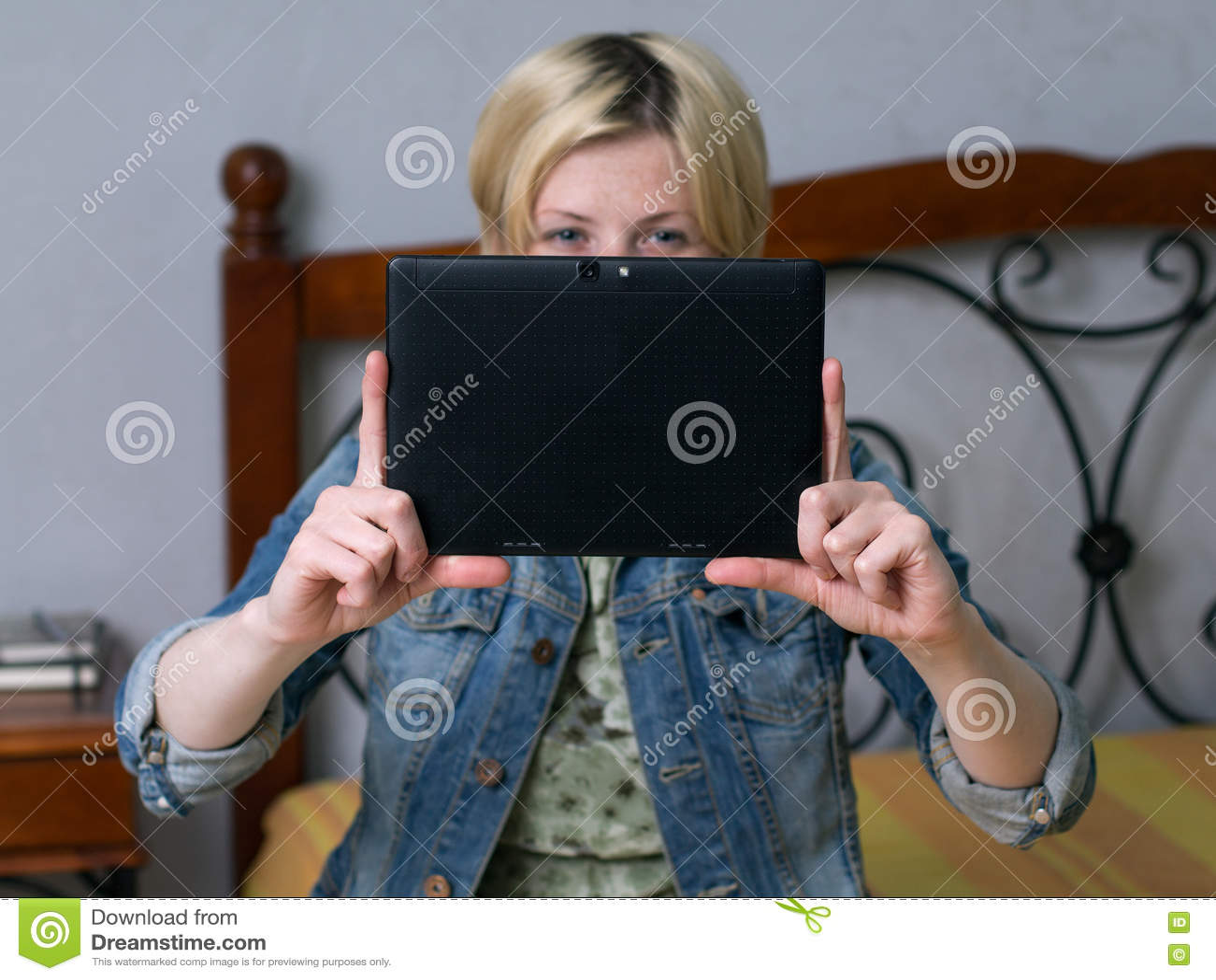 关闭举行片剂和微笑的年轻白肤金发的妇女