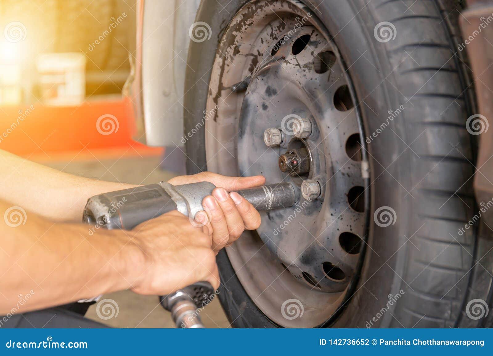 关闭修理技工手在维护期间到气动力学的枪松开汽车轮子坚果改变的轮胎