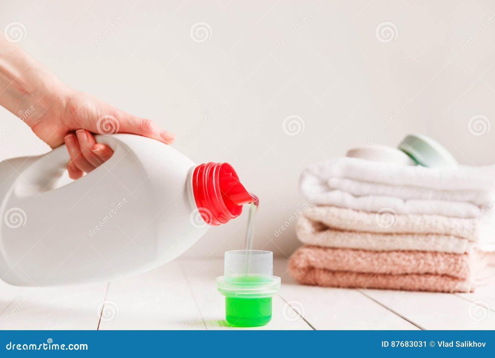 关闭倾吐液体洗涤剂的女性手入在白色土气桌上的盖帽与在背景的毛巾