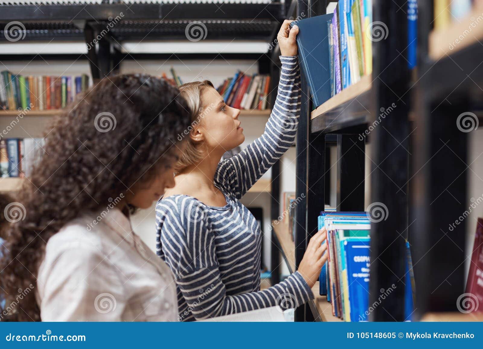 关闭停留近的书架的镶边衬衣的年轻悦目白肤金发的女孩在现代图书馆里,去采取a