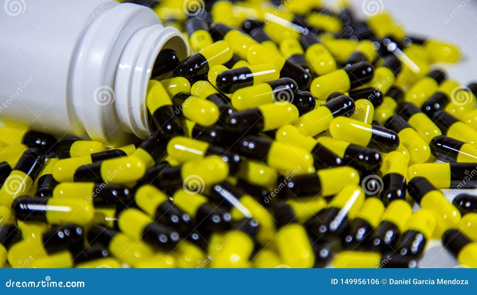 关闭在一个瓶掉下来的处方药 黑和黄色药片