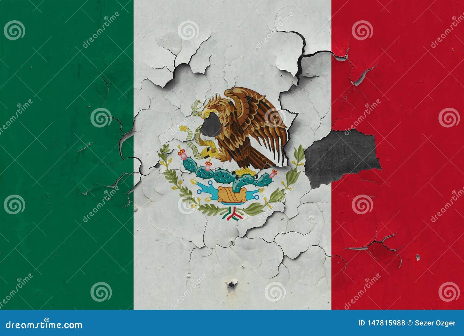 关闭在剥皮油漆的墙壁上的脏,损坏的和被风化的墨西哥旗子看叉瓦的基面