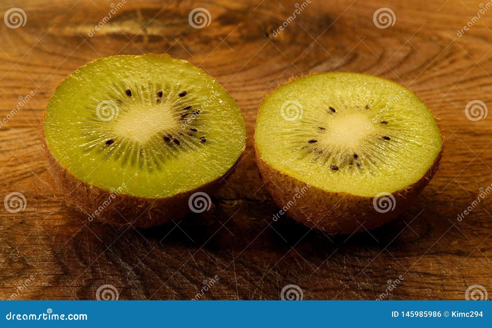 关闭在在一个木切板的一半分裂的猕猴桃 与黑种子的鲜绿色的猕猴桃
