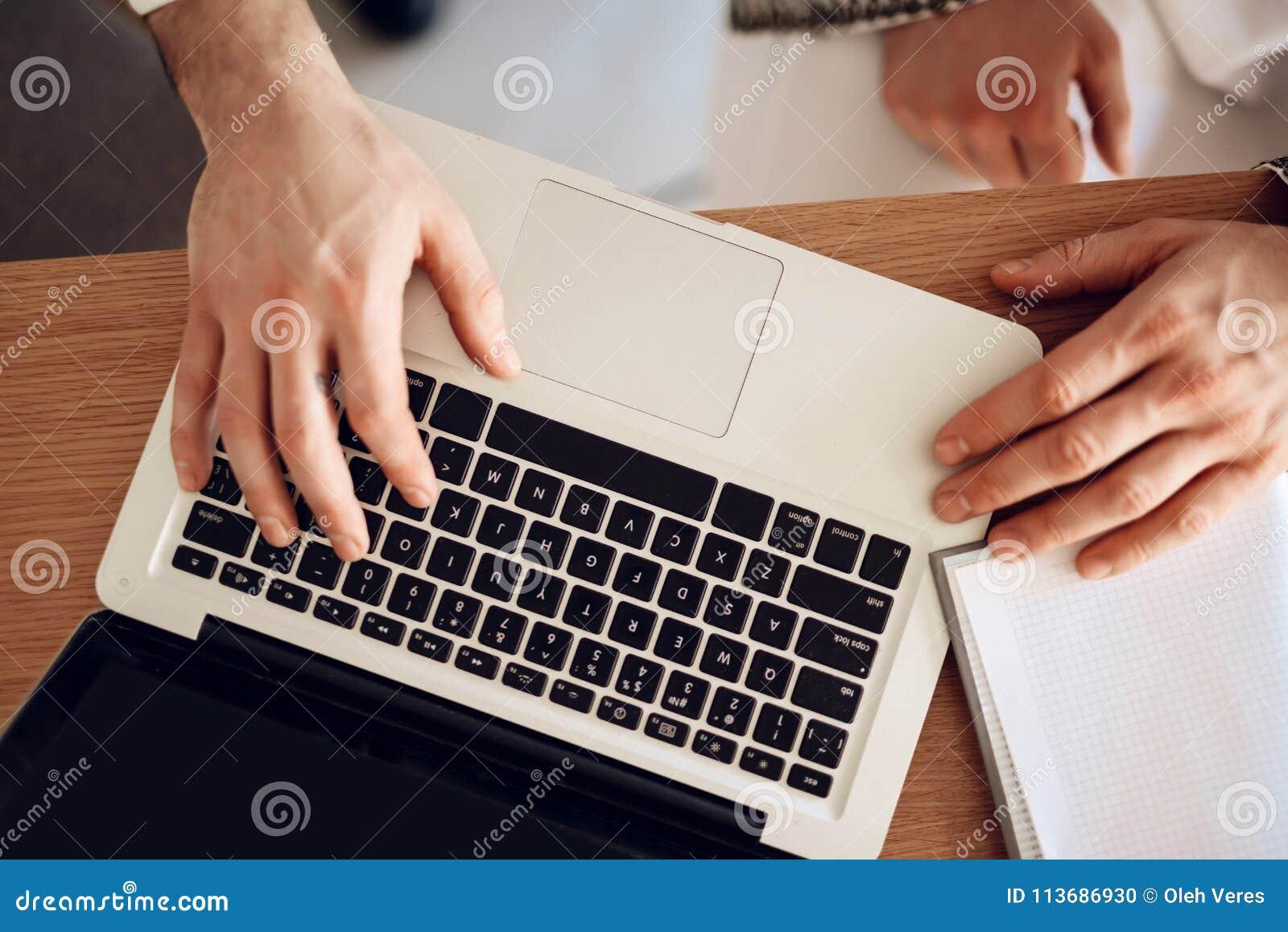 关闭在桌上的膝上型计算机用三只手