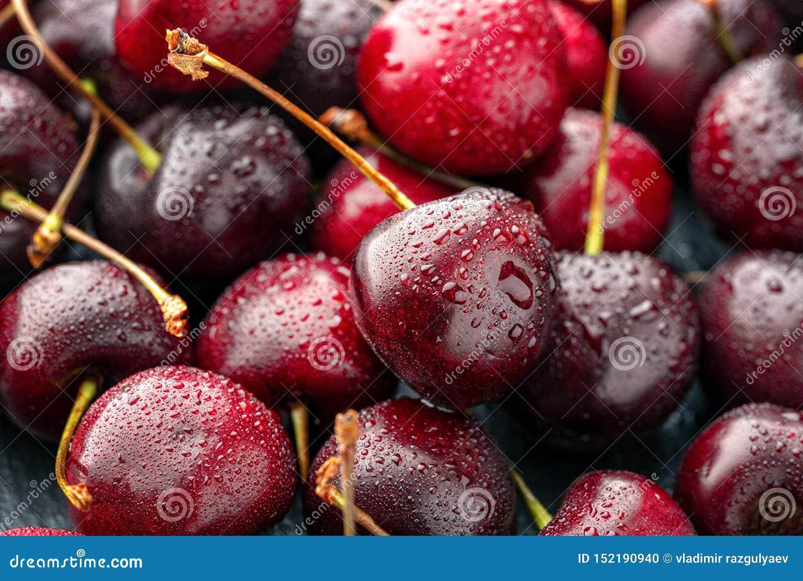 关闭堆与茎的成熟樱桃 新鲜的红色樱桃的大收藏量 成熟樱桃背景