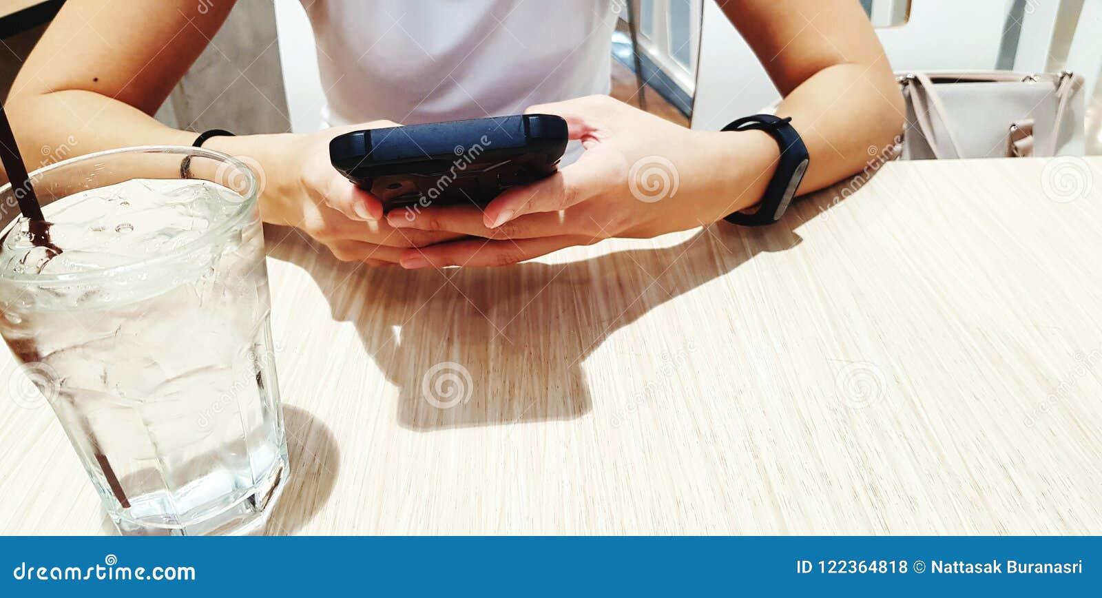 关闭妇女` s手使用有杯的黑巧妙的电话在木桌上的冷水在等待的食物期间在餐馆w