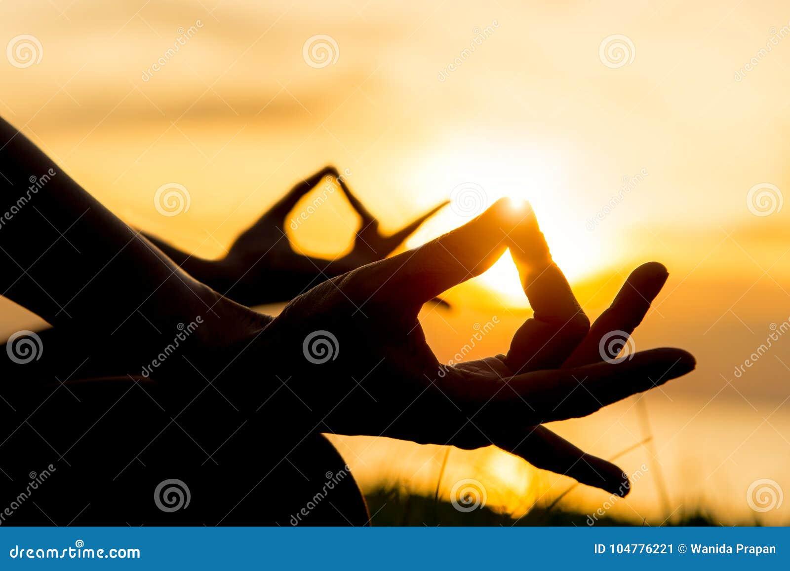 关闭手 妇女做室外的瑜伽 妇女健身生活方式的行使重要和凝思在海滩日落背景中