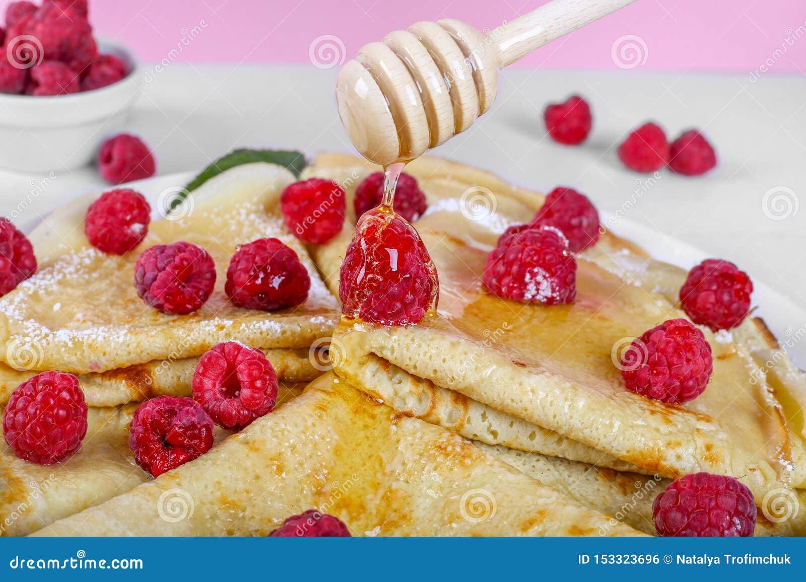 关闭打开顶面用莓和蜂蜜下落在薄煎饼的倾吐的蜂蜜 薄煎饼在木桌和桃红色上