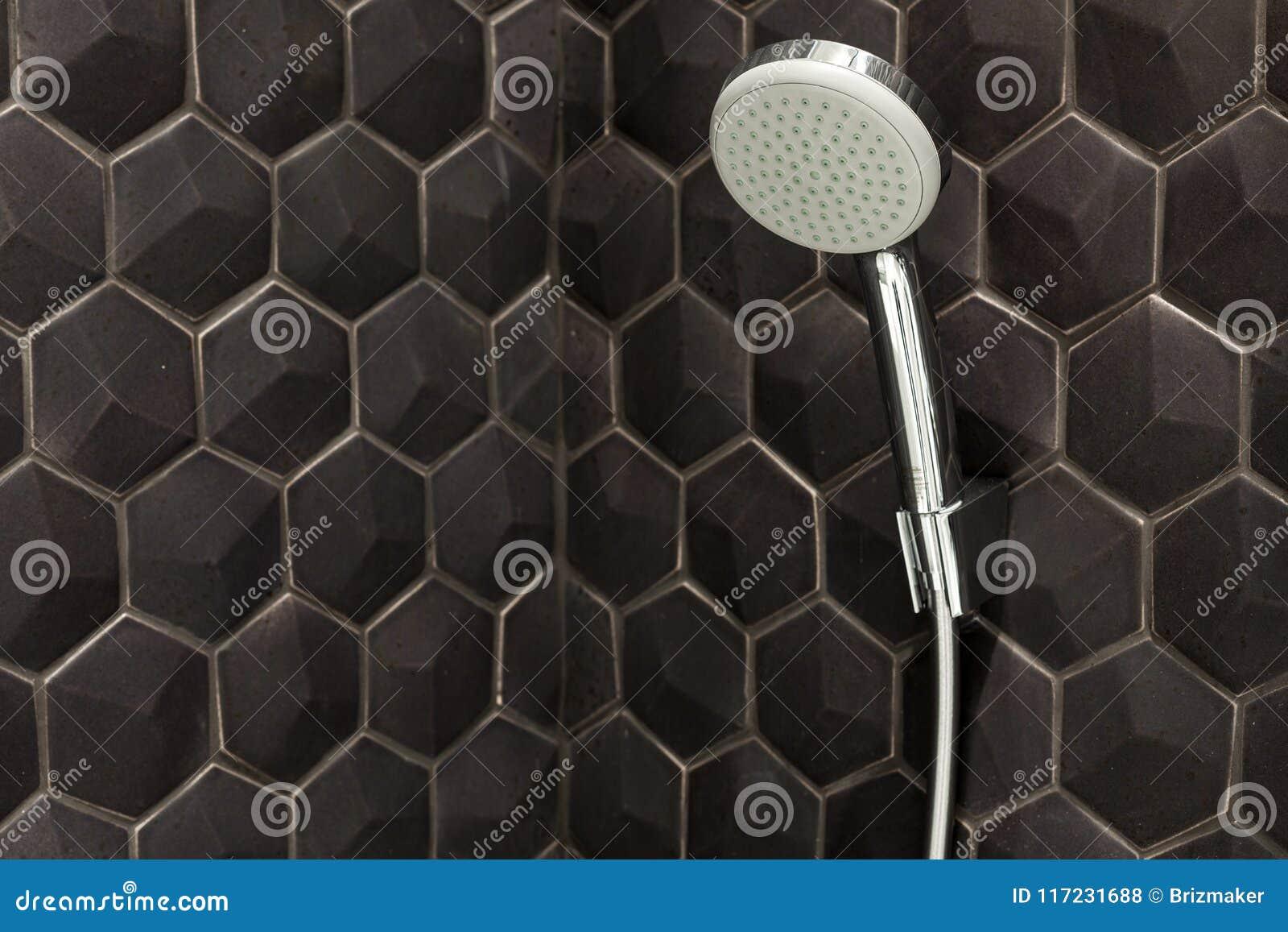 关闭新的阵雨头在卫生间里反对黑瓦片背景