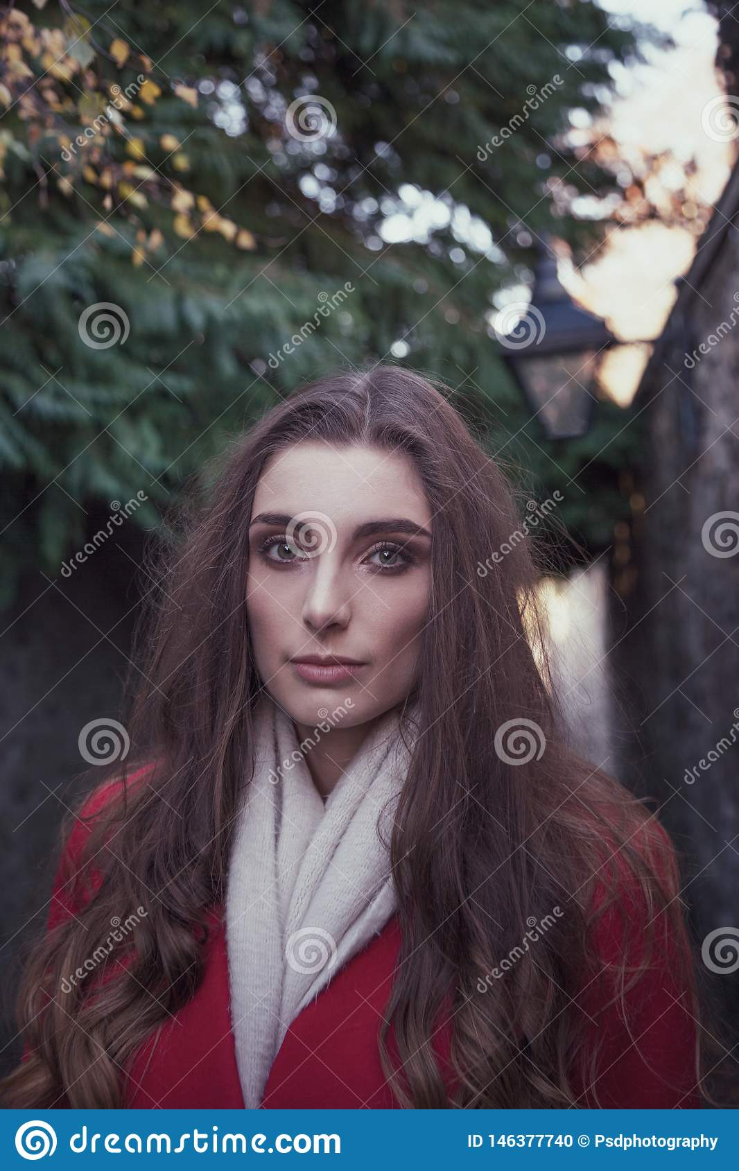 关闭有严肃的神色的一名年轻可爱的妇女在她的面孔