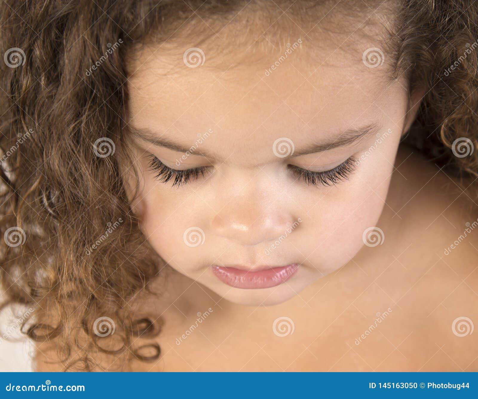 关闭有卷曲,棕色头发的小孩