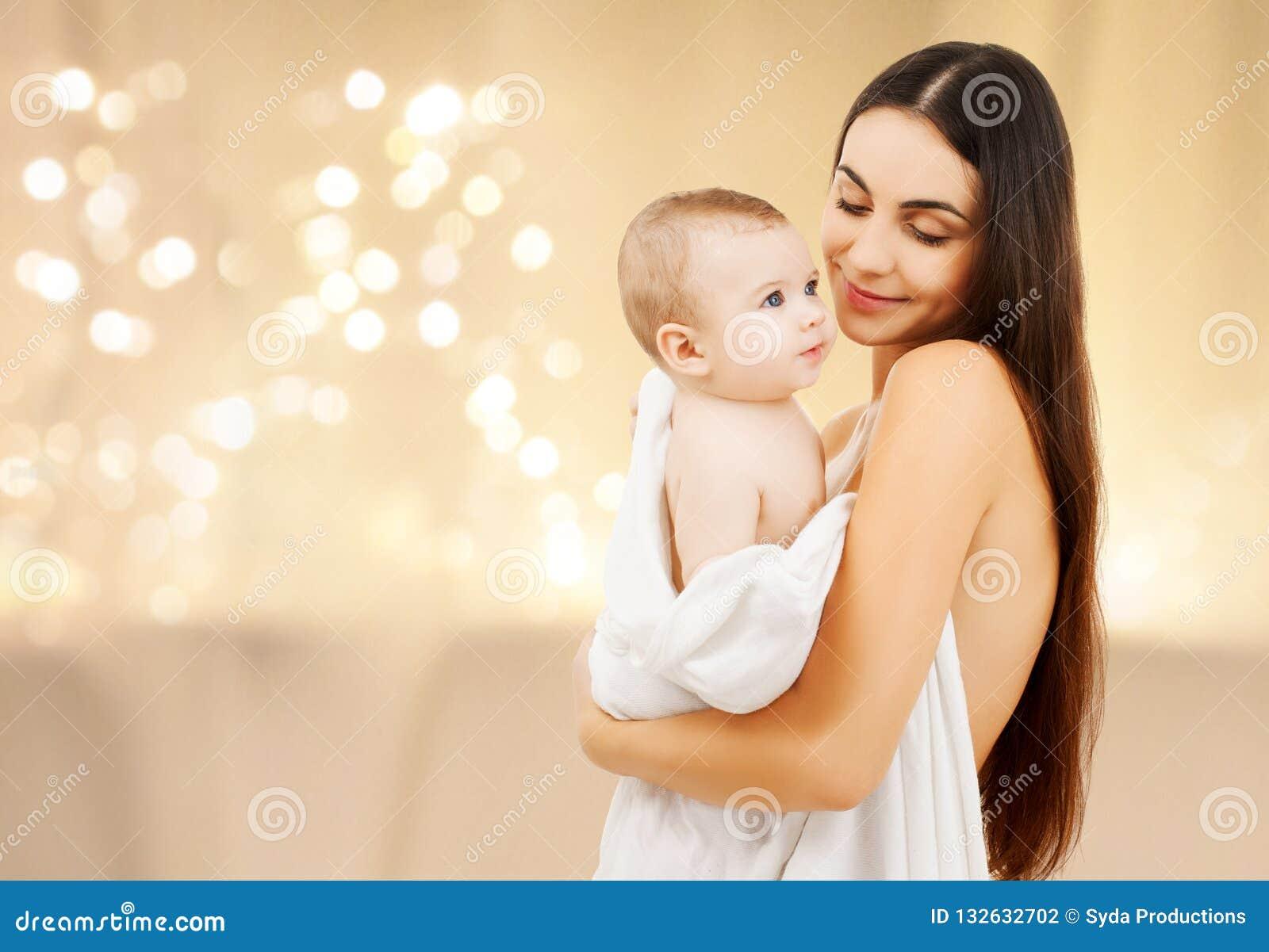 关闭有婴孩的母亲在圣诞灯