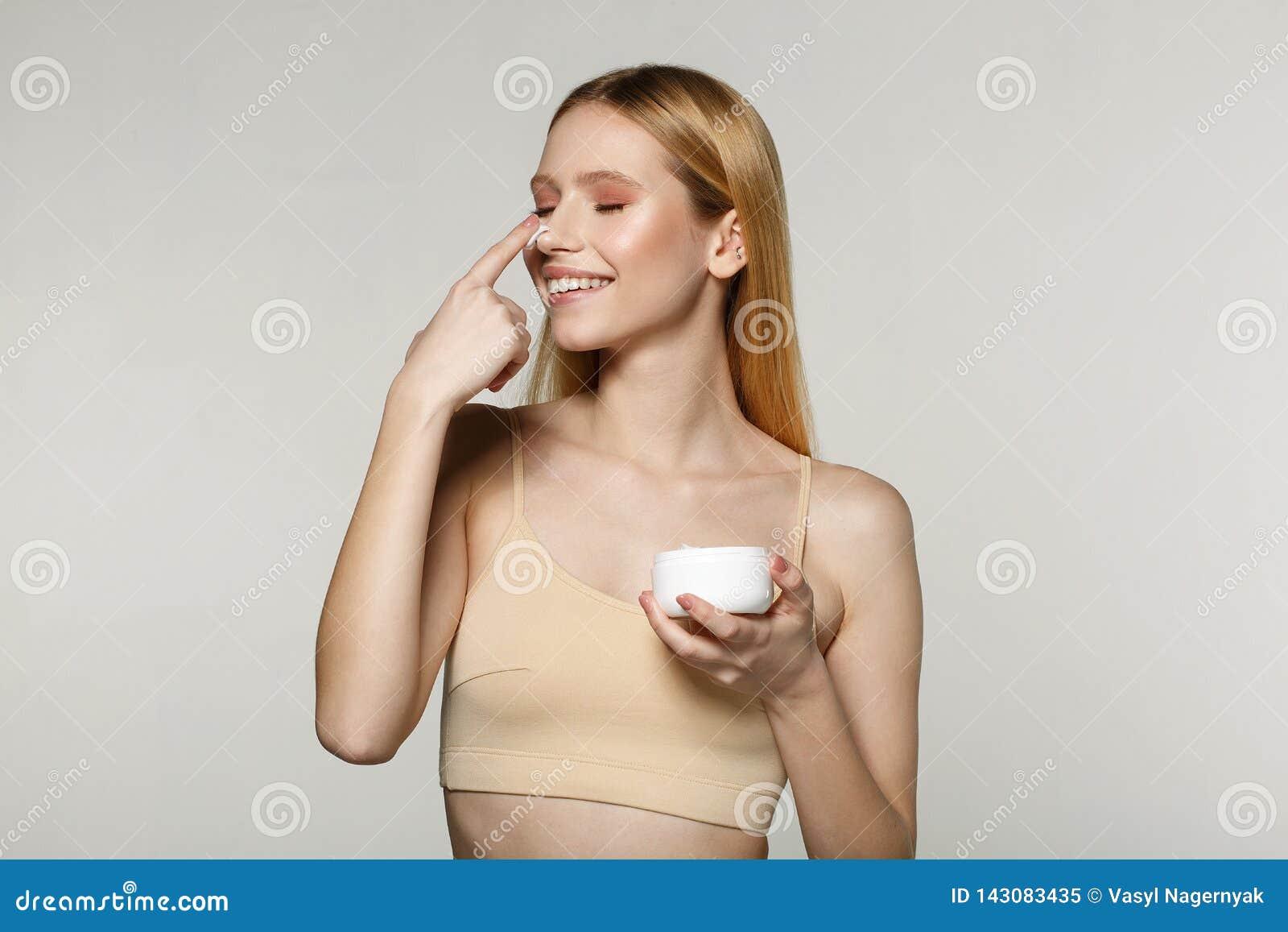 关闭有站立与一个瓶子的金发的正面年轻女人奶油在她的手上