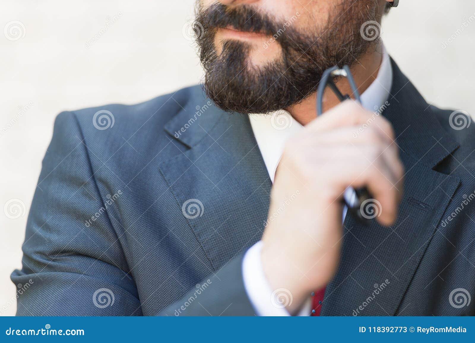 关闭有胡子的下巴手停滞杯在衣服和红色领带的商人 商人认为用近手他的下巴