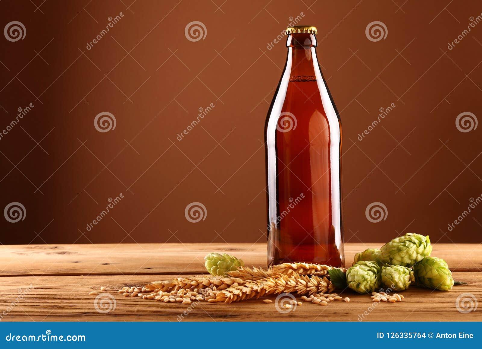 关闭棕色啤酒瓶,蛇麻草,在桌上的大麦