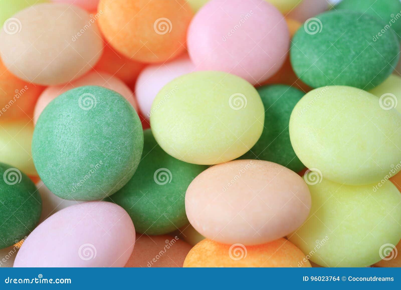 关闭淡色圆的糖果堆,与选择聚焦的背景的