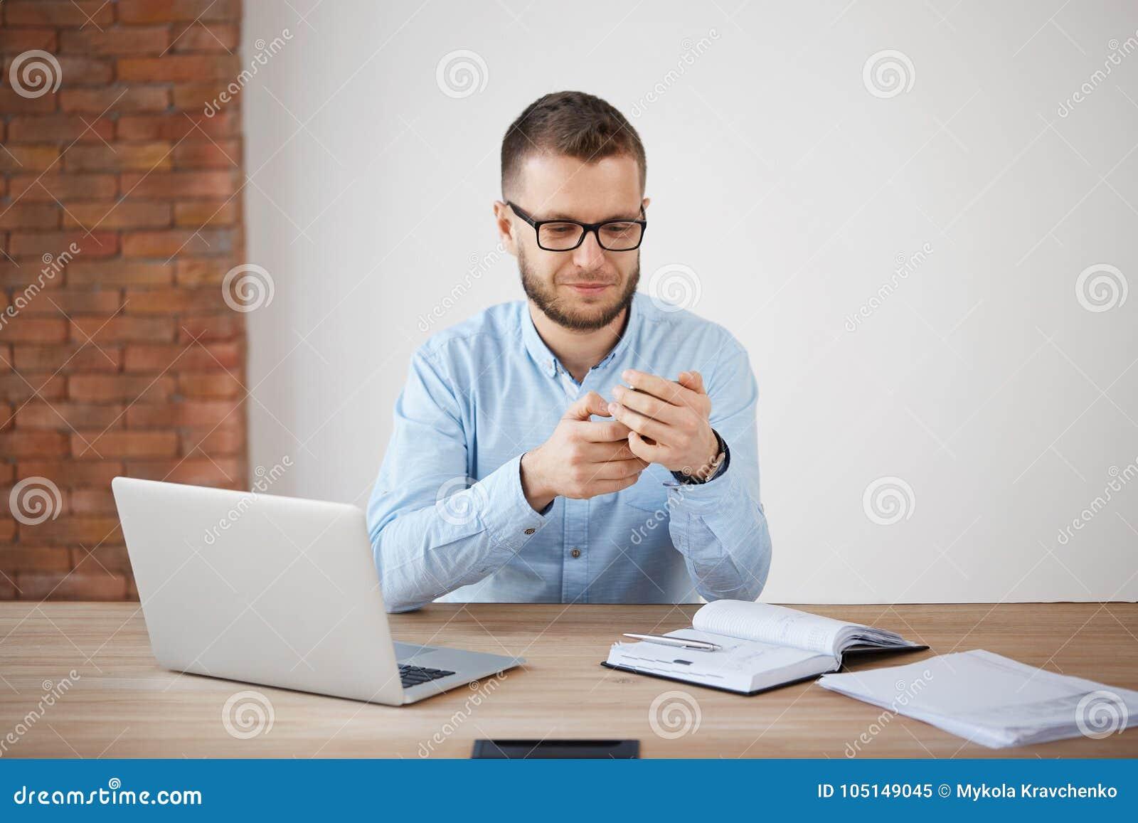 关闭玻璃和衬衣的成熟不剃须的人在工作,聊天与妻子由智能手机在午餐期间 经理