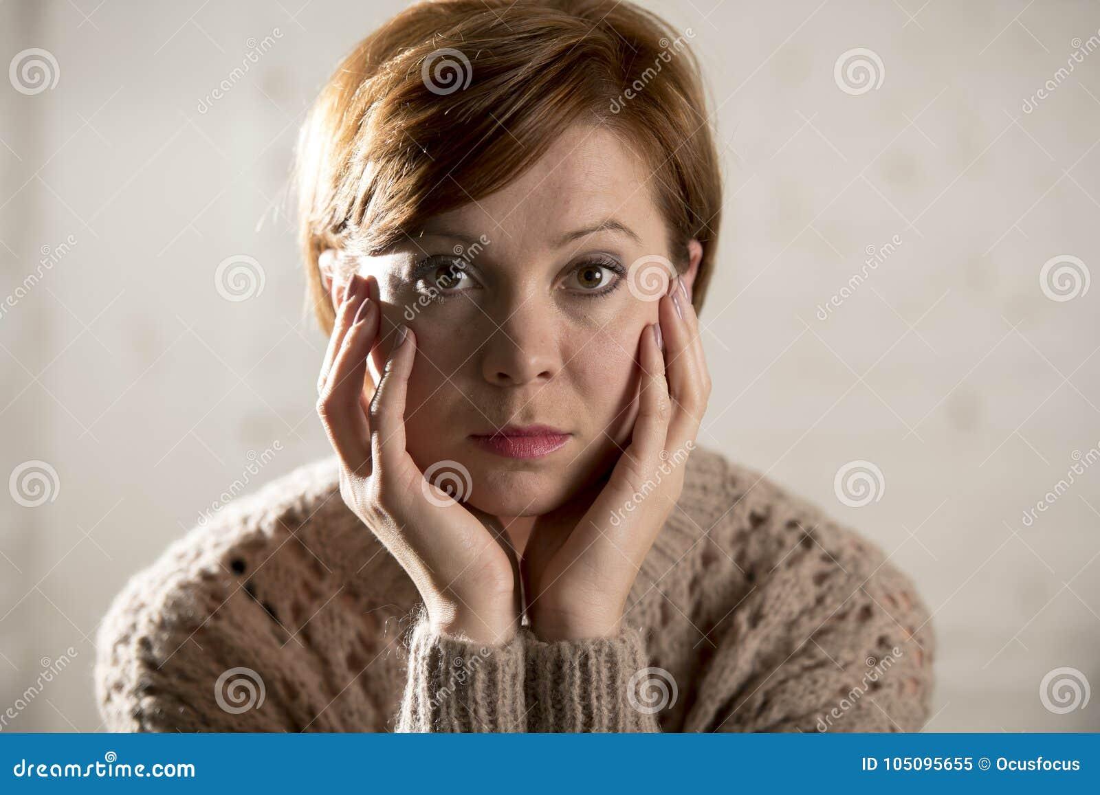 关闭看起来年轻甜和相当红色头发的妇女画象哀伤和沮丧在感到剧烈的面孔的表示偏僻