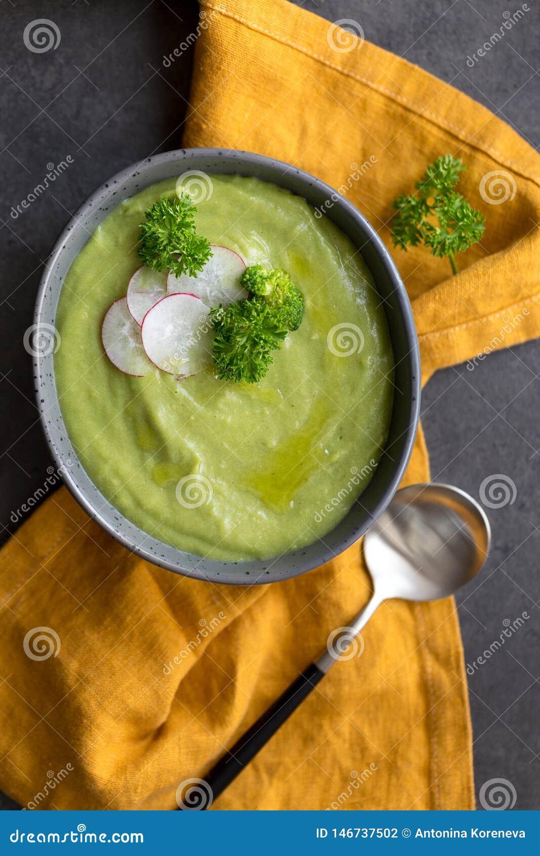 关闭硬花甘蓝奶油色汤用萝卜和匙子在灰色背景